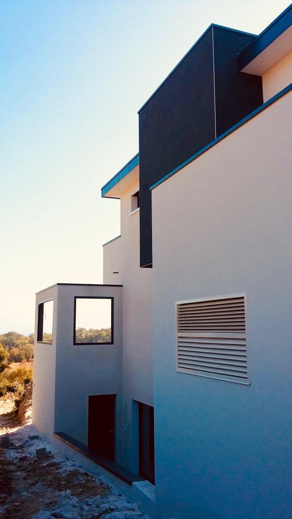 Magnifique construction de maison avec l'intégration de la grille de la pompe à chaleur Amzair SILENZ intérieure