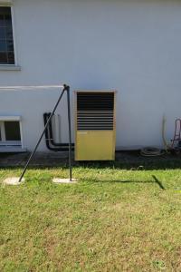 Une pompe à chaleur haute température AMZAIR dans un jardin pour une rénovation en remplacement d'une chaudière fioul